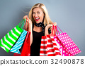 Happy young woman holding shopping bags  32490878