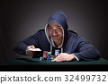 Young man wearing a hoodie with cards and chips 32499732
