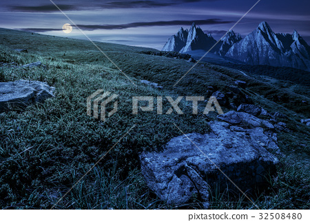 meadow with huge stones on top of mountain range 32508480