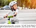 boy in a helmet riding bike 32520782