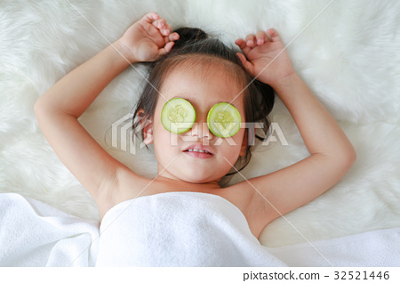 Child girl with a slice of cucumber in her eye 32521446