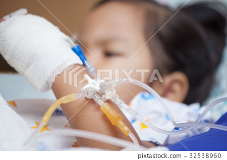 Child's hand with saline intravenous (iv) drip 32538960