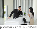 The receptionist greets the young businessman who is about to bo 32568549