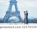 Couple near the Eiffel tower in Paris 32570330