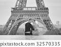 Couple near the Eiffel tower in Paris 32570335