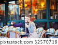 Romantic couple taking selfie in cafe in Paris, France 32570719