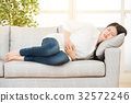 young woman suffering from stomachache on sofa 32572246
