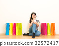 woman sitting on a white wall with wooden floor 32572417