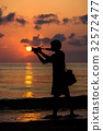 Silhouettes of photographers with the sunrise. 32572477
