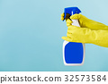 Hand in yellow glove holds  spray bottle of liqui 32573584