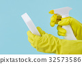 Hand in yellow glove holds spray bottle of liquid 32573586