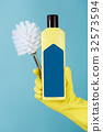 Hand in yellow glove holds bottle of liquid 32573594