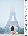 Parisian woman in front of the Eiffel tower 32574580