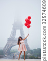 Parisian woman with red balloons in front of the Eiffel tower 32574609