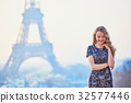 Parisian woman near the Eiffel tower at morning 32577446