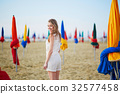 Woman with famous colorful parasols on Deauville Beach in France 32577458