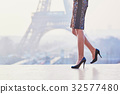 Woman walking near the Eiffel tower 32577480