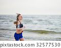 Young fitness running woman jogging on beach 32577530