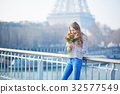 Girl with bunch of red tulips near the Eiffel tower 32577549