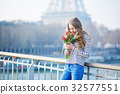 Girl with bunch of red tulips near the Eiffel tower 32577551