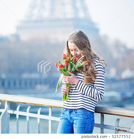 Girl with bunch of red tulips near the Eiffel tower 32577552