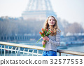 Girl with bunch of red tulips near the Eiffel tower 32577553