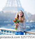 Girl with bunch of red tulips near the Eiffel tower 32577554