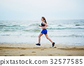 Young fitness running woman jogging on beach 32577585