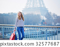 Young girl with shopping bags near the Eiffel tower 32577687