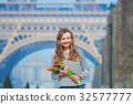 Girl with bunch of red tulips near the Eiffel tower 32577777