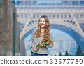 Beautiful young girl with red tulips near the Eiffel tower 32577780