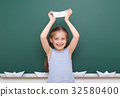 Pupil posing at school board, education concept  32580400