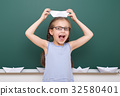 Pupil posing at school board, education concept  32580401