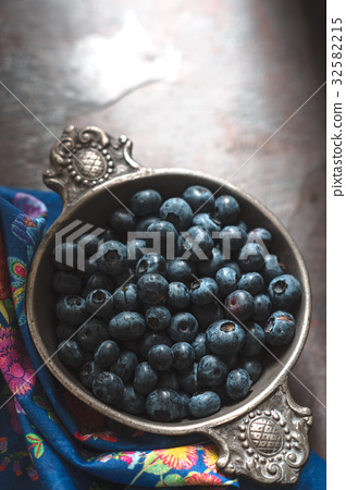Blueberries in a tin bowl and napkin on slate 32582215