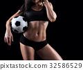 Fitness model holding soccer ball 32586529