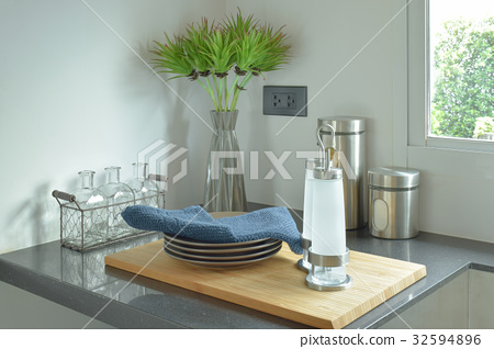 Dishes and bottles on black counter top in kitchen 32594896