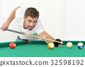 young man playing billiard 32598192