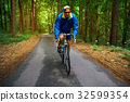 Man is riding a road bike along a forest road 32599354