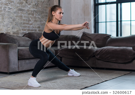 Beautiful fit girl doing home workout performing 32600617