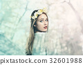 Beautiful woman with a flower garland and a white 32601988