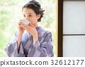 A woman in kimono drinking tea 32612177