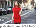 Young blonde woman walking in the street 32614627