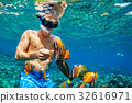 Young man snorkeling with coral reef fishes 32616971