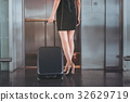 Charming girl is going in elevator with her 32629719