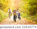 Young family in warm clothes cycling in autumn 32630774