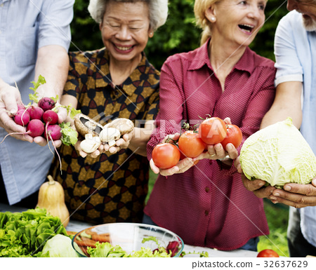 Diverse senior people holding vegetables in their hands 32637629