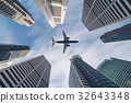 Airplane flying over city business buildings, high-rise skyscrap 32643348