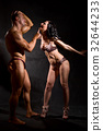 Muscular man and a woman posing in studio 32644233