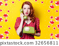 girl in red dress with green dial phone 32656811