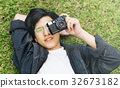 Asian guy lay down and takes photo with camera 32673182